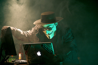 Anonymous hacker on laptop